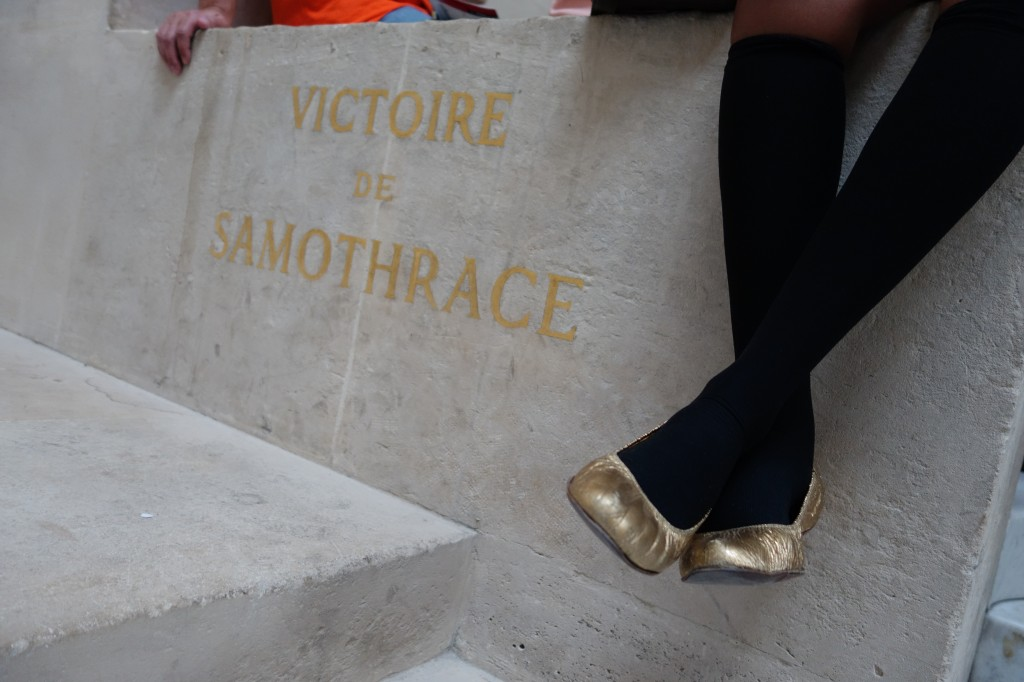 Frau Kolb Takes in The Winged Victory of Samothrace in Paris, France